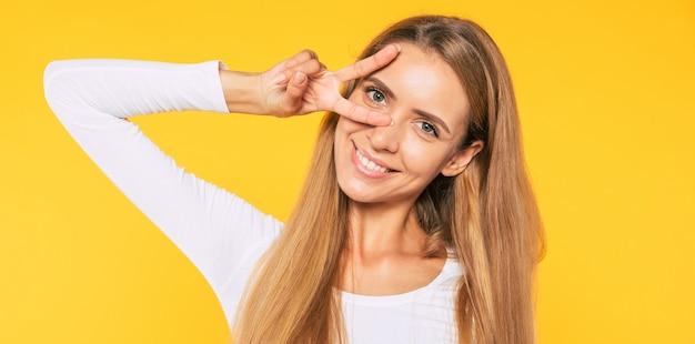 Com vitória e paz no coração. mulher atraente mostrando gesto de paz enquanto fica de pé na parede amarela