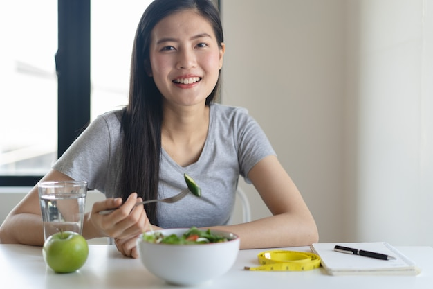 Coma alimentos saudáveis no estilo de vida de bem-estar. mulher comendo salada.