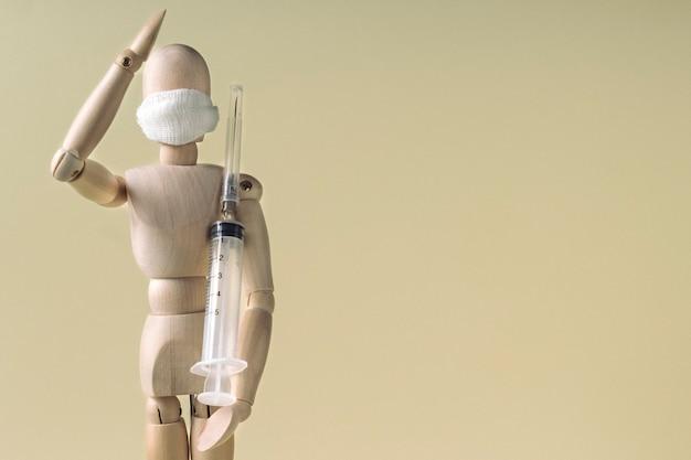 Combate ao coronavírus. manequim de madeira segurando a seringa e saudando como soldado amarelo