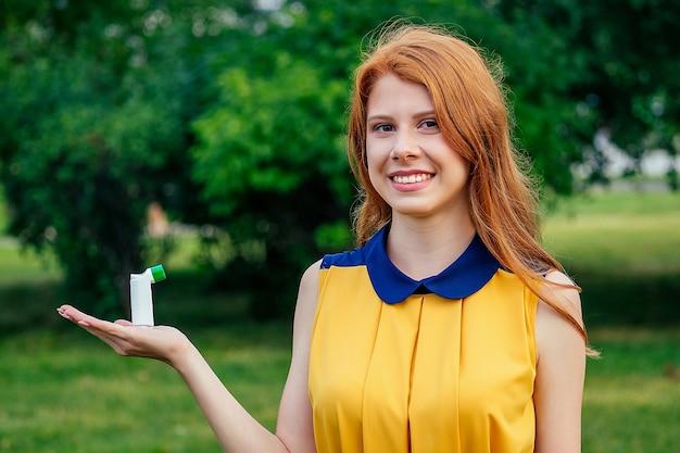 Combatendo a asma e a bronquite. ativo alegre linda jovem ruiva ruiva irlandesa mulher norueguesa em um vestido amarelo, segurando o inalador na mão no parque de verão. conceito de alergia de primavera
