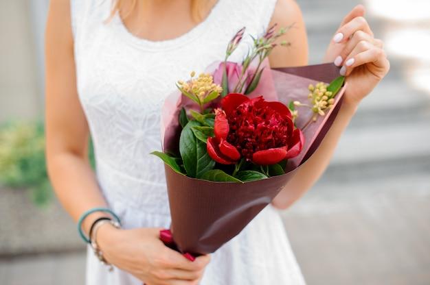Combinação de flores coloridas nas mãos da mulher