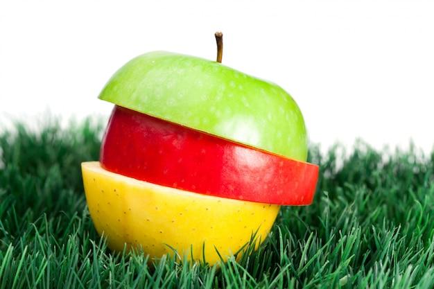 Combinação de maçãs verdes, amarelas e vermelhas na grama