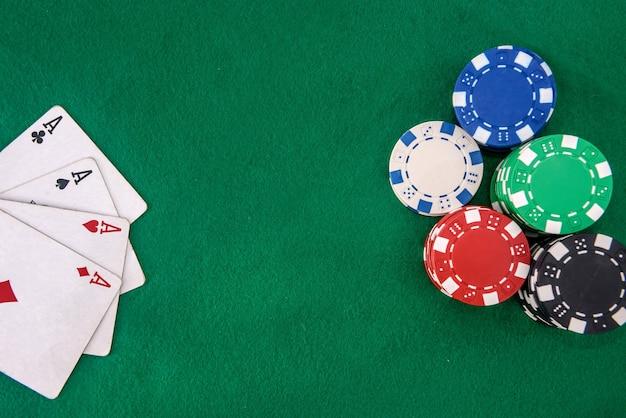 Combinação de quatro ases com fichas de pôquer na mesa verde