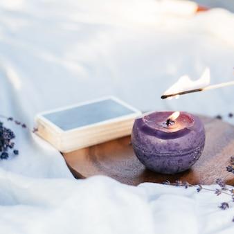 Combine as velas das luzes com ao lado do baralho de cartas e flores de lavanda, na superfície branca e de madeira