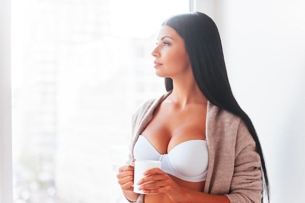 Começando o dia com café fresco. mulher jovem e bonita em lingerie e suéter segurando a xícara de café e olhando pela janela