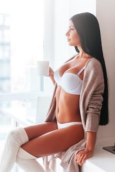 Começando um novo dia com café fresco. mulher jovem e bonita em lingerie e suéter segurando a xícara de café e desviando o olhar enquanto está sentada no balcão da cozinha perto da janela