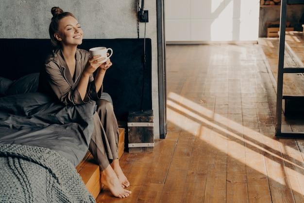 Começando um novo lindo dia. mulher bonita bonita com uma xícara de café da manhã esfriando enquanto está sentado na cama, relaxando em um pijama de cetim marrom em apartamento moderno. momentos felizes em casa