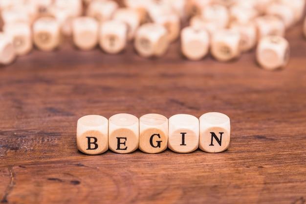 Comece a palavra em cubos de madeira