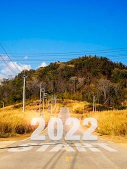 Comece com o novo ano de 2022, palavras grandes e números na estrada local aberta para a montanha grande para superar obstáculos, sucesso, futuro, estilo vertical. comece e começando com o conceito de objetivo de negócios.