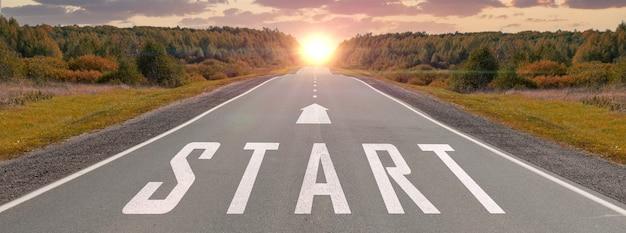 Comece escrito na estrada rodoviária no meio de uma estrada de asfalto vazia e um lindo céu ao pôr do sol