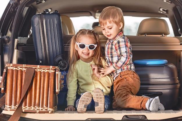 Começo da viagem crianças fofas brincando no porta-malas de um carro com
