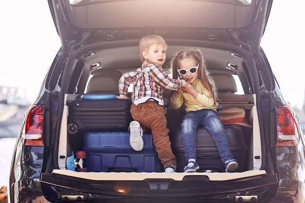 Começo da viagem crianças fofas no porta-malas de um carro com malas