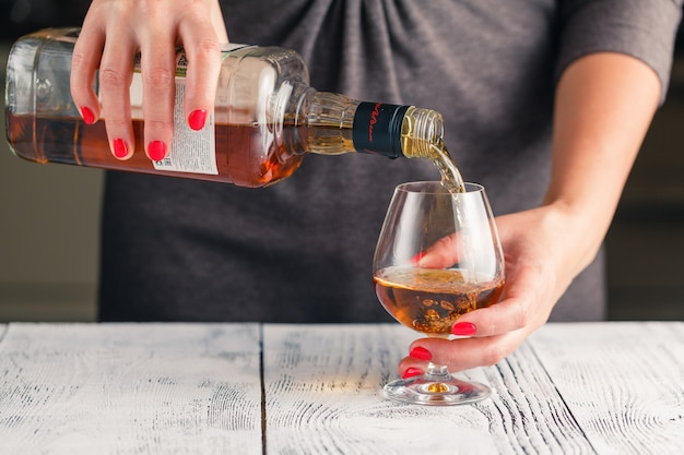 Começo do alcoolismo. fêmea tomar copo de vinho na mesa tonificada escura