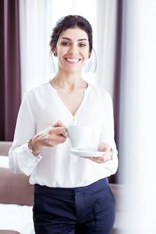 Começo do dia. mulher de negócios confiante bebendo uma xícara de café enquanto começa seu dia de trabalho