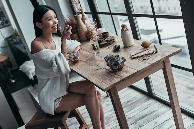 Começo saudável do dia. vista superior de uma jovem atraente tomando café da manhã saudável Foto Premium