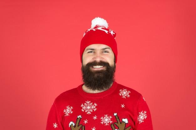 Começou a liquidação de natal. homem barbudo em fundo de chapéu vermelho. hipster maduro em uma camisola de malha. use roupas quentes nesta temporada. está frio lá fora. atmosfera de férias de inverno. retrato de homem feliz santa.