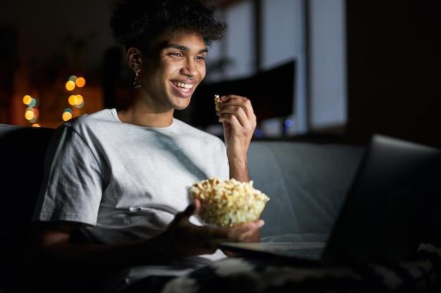 Comédia feliz jovem sorrindo assistindo um filme online usando um laptop e comendo pipoca enquanto está sentado