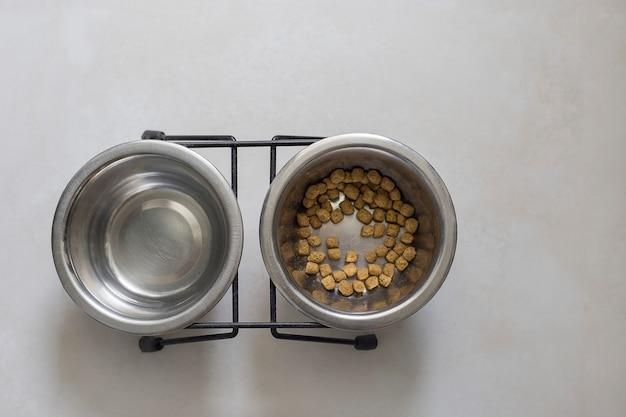Comedouro para animais comida para gatos duas tigelas com comida para gatos e suporte para água no chão, vista de cima