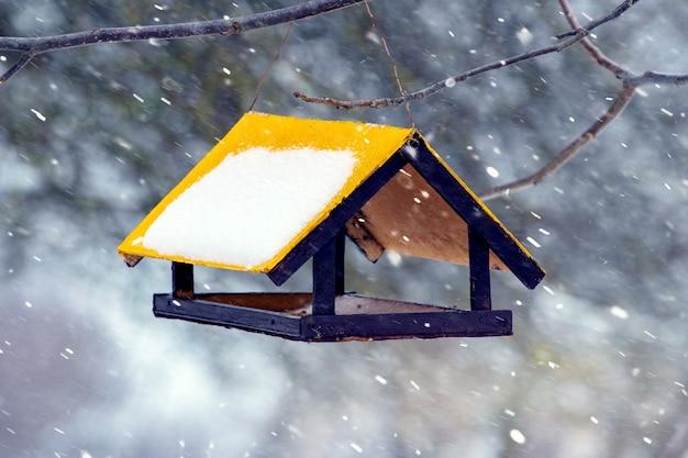 Comedouro para pássaros no jardim no inverno durante uma nevasca