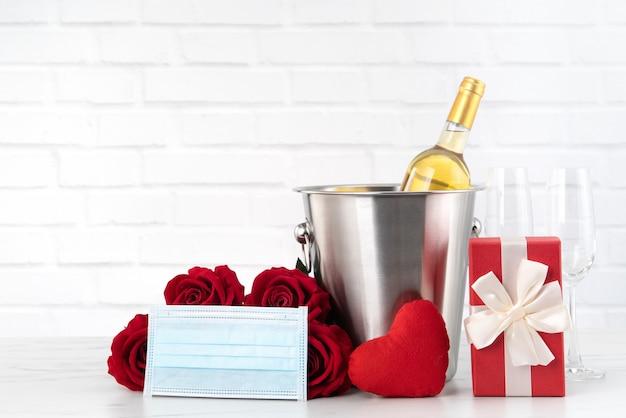 Comemoração do dia dos namorados com conceito de proteção de vinho, buquê e máscara facial durante esse período difícil.