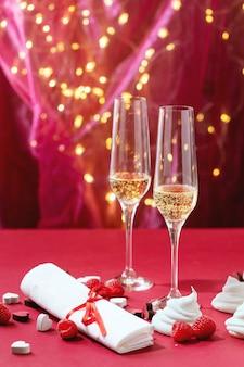 Comemoração do dia dos namorados com duas taças de champanhe em bokeh claro e fundo de textura vermelha