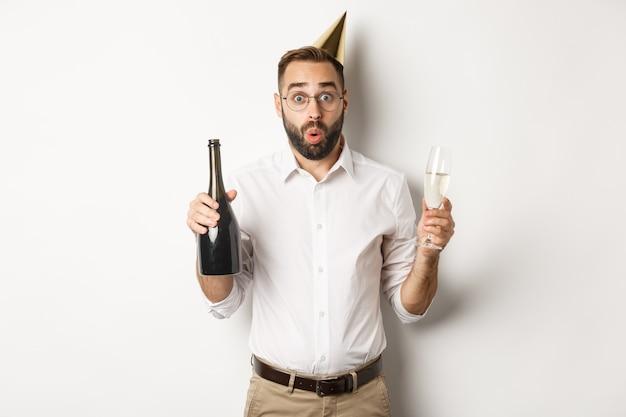 Comemoração e feriados. homem surpreso com chapéu de aniversário, segurando champanhe e taça e parecendo espantado, em pé sobre um fundo branco.