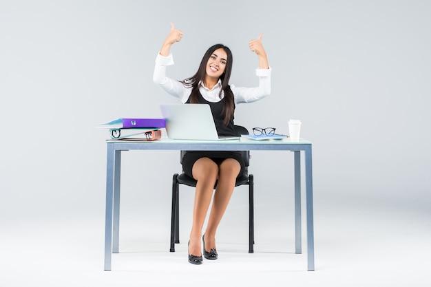 Comemorando a empresária sentada na mesa com o laptop isolado no branco