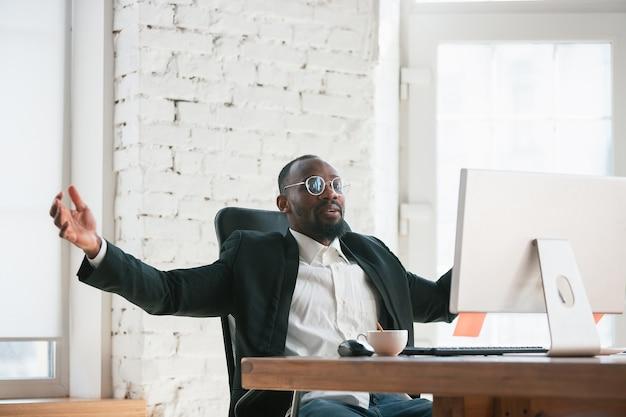 Comemorando a vitória. empreendedor afro-americano, empresário trabalhando concentrado no escritório. parece feliz, alegre, vestindo terno clássico, jaqueta. conceito de trabalho, finanças, negócios, liderança de sucesso