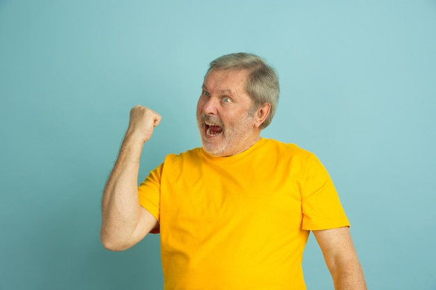 Comemorando a vitória, esporte. retrato de homem caucasiano isolado no fundo azul do estúdio. lindo modelo masculino posando de camisa amarela.