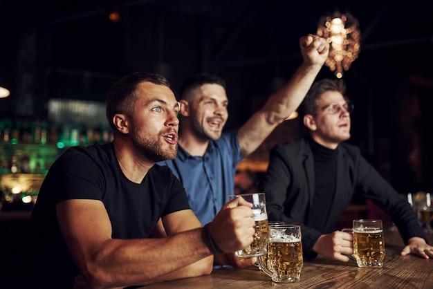 Comemorando a vitória. três fãs de esportes em um bar assistindo futebol. com cerveja nas mãos.