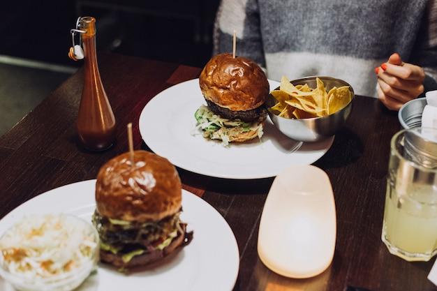 Comemorando com um suculento hambúrguer de carne em um restaurante