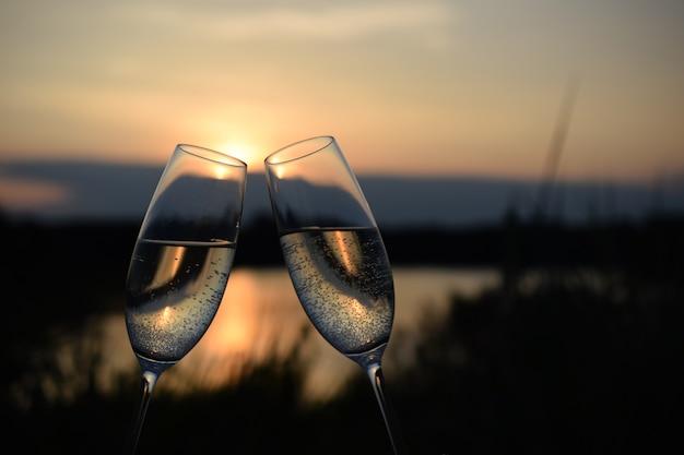 Comemorando o ano novo com duas taças de vinho ao pôr do sol à beira do lago com espaço para texto