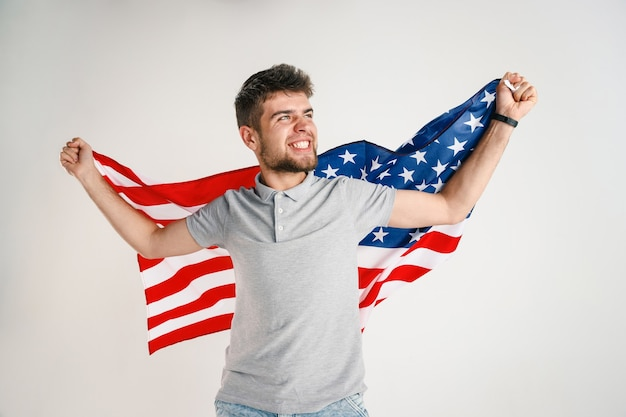 Comemorando o dia da independência. estrelas e listras. jovem com bandeira dos estados unidos da américa, isolada na parede branca do estúdio. parece muito feliz e orgulhoso como um patriota de seu país.