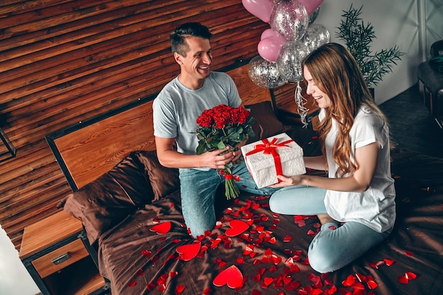 Comemorando o dia dos namorados. um homem dá um presente a uma mulher e rosas vermelhas. um casal está sentado na cama com confetes em forma de coração.