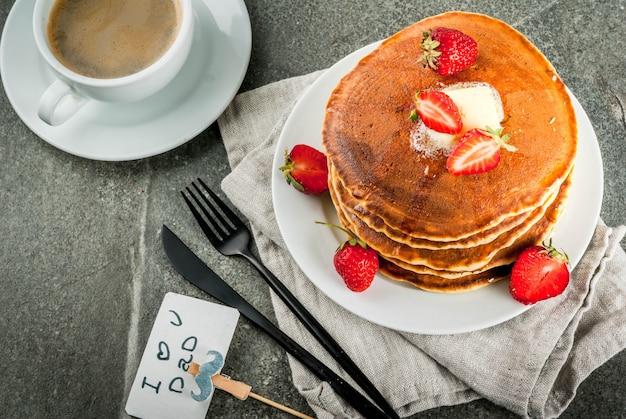 Comemorando o dia dos pais. café da manhã. a idéia para um café da manhã saudável e delicioso: panquecas com manteiga, xarope de bordo e morangos frescos, com parabéns. xícara de café. copyspace