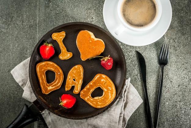 Comemorando o dia dos pais. café da manhã. a idéia para um café da manhã saudável e delicioso: panquecas em forma de parabéns - eu amo papai. em uma frigideira, caneca de café e morangos. vista superior copyspace
