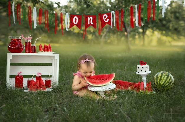 Comemorando o primeiro aniversário de uma criança na natureza com um bolo e melancias