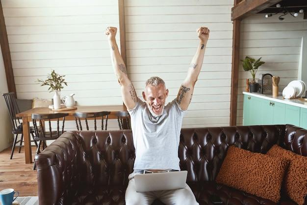 Comemorando o sucesso animado homem de meia-idade em roupas casuais, olhando para a tela do laptop e levantando