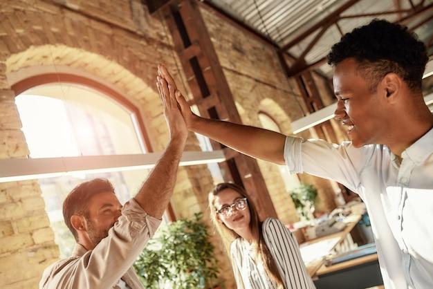 Comemorando o sucesso de dois homens alegres dando highfive enquanto estavam com colegas no moderno