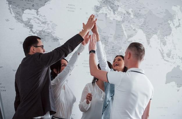Comemorando o sucesso. equipe de freelancers em pé contra a parede com o mapa do mundo nela