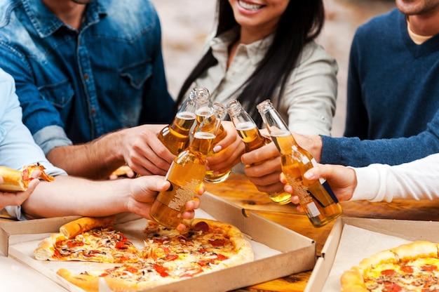 Comemorando sua amizade. close de um grupo de jovens comendo pizza e tilintando copos com cerveja ao ar livre
