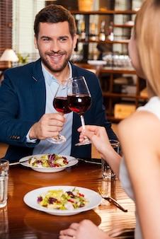 Comemorando sua data especial. jovem casal apaixonado brindando com vinho tinto e sorrindo enquanto estão sentados juntos no restaurante