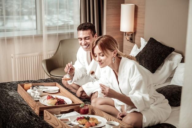 Comendo e rindo. lindo casal apaixonado tomando um café da manhã saboroso e rindo enquanto planeja o dia