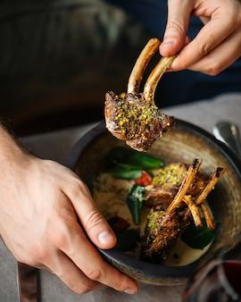 Comendo grelha de cordeiro gourmet assado com ervas e molho