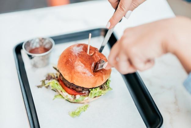 Comendo hambúrguer com um garfo e uma faca.