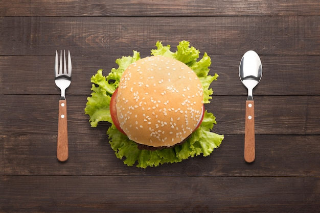 Comendo hambúrguer de churrasco no fundo de madeira