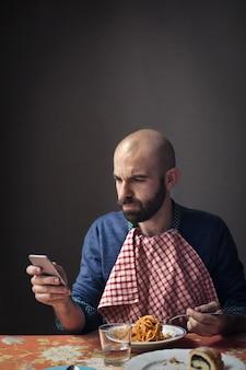 Comendo macarrão e verificando o telefone