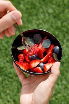 Comendo morangos e uvas em uma tigela preta. lanche saudável.