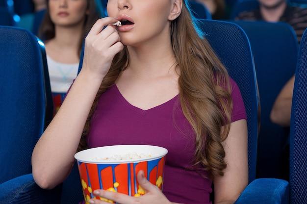 Comendo pipoca no cinema. imagem recortada de uma bela jovem comendo pipoca e assistindo um filme enquanto está sentado no cinema