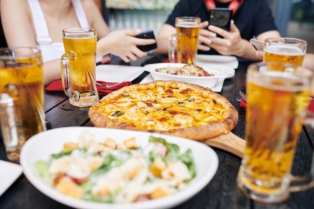 Comendo pizza e bebendo cerveja em um café